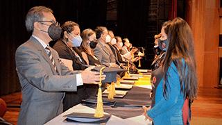 Autoridades colocando el birrete a los nuevos profesionales artesanales